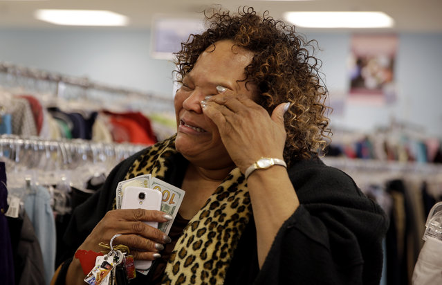 Debra Harris cries after receiving $200 from an anonymous man know known as Secret Santa, Wednesday, December 9, 2015, in Jennings, Mo. Secret Santa is an anonymous Kansas City-area man who hands out $100 bills to the needy during the holiday season and is following in the footsteps his predecessor, Larry Stewart, who, over a quarter-century, gave away over $1 million before dying from cancer in 2007. (Photo by Jeff Roberson/AP Photo)