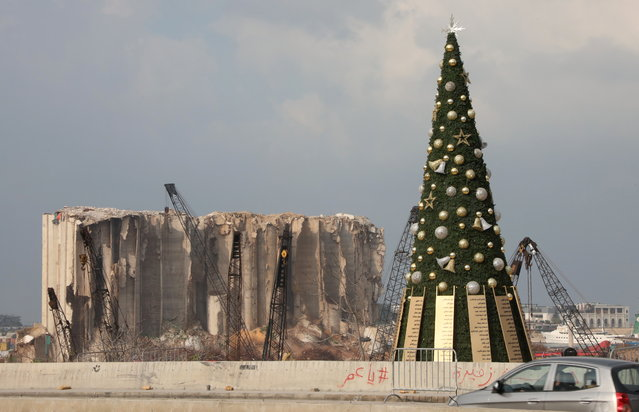 A Christmas tree with names of those who died during Beirut port explosion, is seen near the damaged grain silo, in Beirut, Lebanon on December 22, 2020. (Photo by Mohamed Azakir/Reuters)