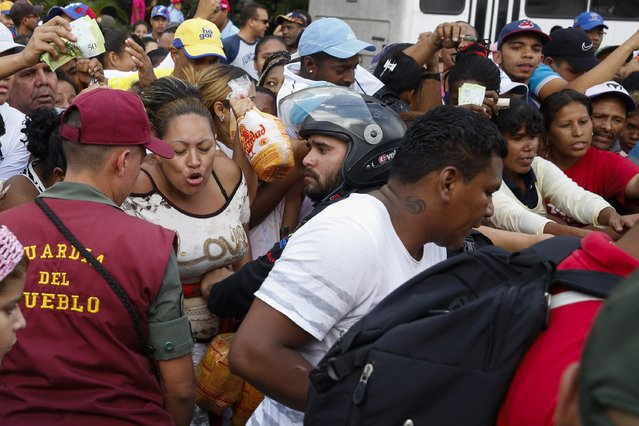 People crowd together in an attempt to buy chickens at a Mega-Mercal, a subsidized state-run street market, in Caracas January 24, 2015. (Photo by Carlos Garcia Rawlins/Reuters)
