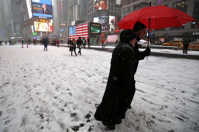 People walk through falling snow through Times Square in New York, January 26, 2015. (Photo by Mike Segar/Reuters)