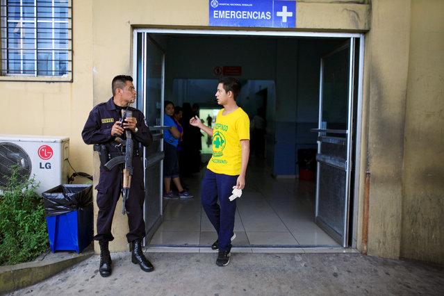 Comandos de Salvamento rescuer Alcides Altamirano speaks with a policeman outside a hospital where they delivered a suspected gang member after he was shot near the Comandos de Salvamento base in San Salvador, El Salvador August 15, 2016. (Photo by Jose Cabezas/Reuters)