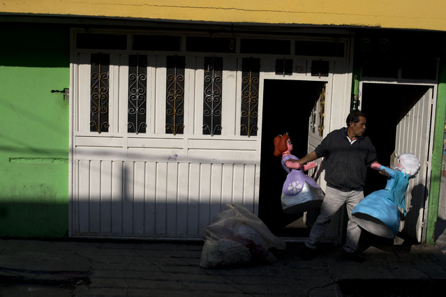In this January 23, 2015 photo, Melesio Vicente Flores carries piñatas designed to look like Disney princesses Elsa and Sofia, to his truck as he prepares a delivery to market vendors, at his home in the Iztapalapa neighborhood of Mexico City. Despite some past problems with copyright infringement crackdowns, piñata makers say they have to make the characters their clients want. (Photo by Rebecca Blackwell/AP Photo)