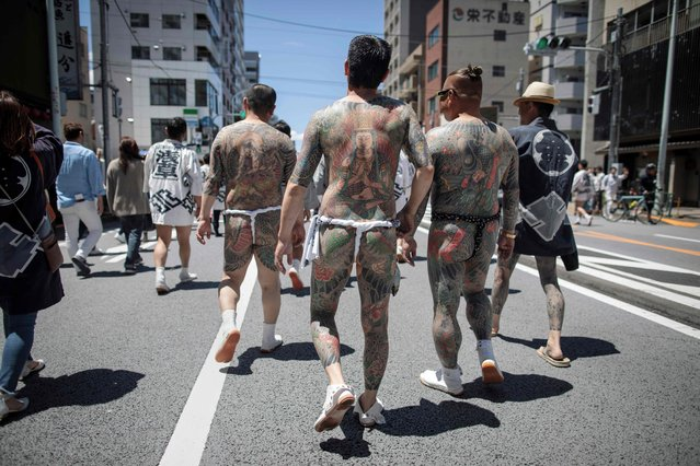Participants with traditional Japanese tattoos (Irezumi), related to the Yakuza, walk through the Asakusa district during the annual Sanja Matsuri festival in Tokyo on May 20, 2018. Sanja Matsuri festival is a celebration for the three founders of Sensoji Temple in the Asakusa neighbourhood with nearly two million people visiting during the three-day event. (Photo by Behrouz Mehri/AFP Photo)