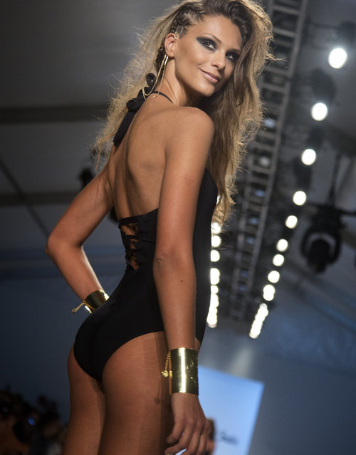 In Friday, July 19, 2013 photo, a model walks the runway during the Dolores Cortes show at the Mercedes-Benz Fashion Week Swim show in Miami Beach, Fla. (Photo by J. Pat Carter/AP Photo)
