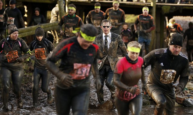 Competitors run through mud during the Tough Guy event in Perton, central England February 1, 2015. (Photo by Phil Noble/Reuters)