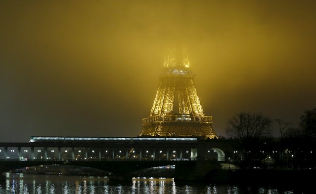 The Eiffel Tower is engulfed in fog early morning in Paris, December 14, 2015. (Photo by Gonzalo Fuentes/Reuters)