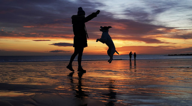 A woman throws a ball for her dog as the sun rises at Tynemouth Longsands beach in Tyne and Wear on the North East coast on Friday, March 12, 2021. (Photo by Owen Humphreys/PA Images via Getty Images)