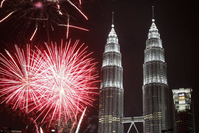 Fireworks explode in front of Malaysia's landmark building, Petronas Twin Towers, during the New Year's Eve celebration in Kuala Lumpur, Malaysia, Friday, January 1, 2016. (Photo by Joshua Paul/AP Photo)