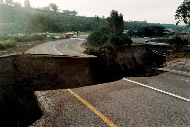 A sinkhole which damaged an on-ramp to Interstate 15 in San Diego on February 24 continues to grow February 25, 1998. The hole was caused by a drainage pipe which burst due to heavy rains attributed to El Nino weather patterns and is approximately eight hundred feet long, forty feet wide, and seventy feet deep. (Photo by Reuters)