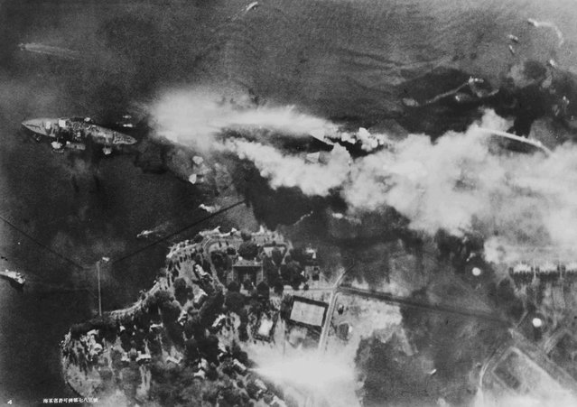 The battleship USS Arizona burns on Battleship Row, beside Ford Island in an aerial photo taken from a Japanese aircraft during the attack on Pearl Harbor, Hawaii, U.S. December 7, 1941. Ships seen are (L-R) USS Nevada, USS Arizona with USS Vestal moored outboard, USS Tennessee with USS West Virginia moored outboard and USS Maryland with USS Oklahoma capsized alongside. (Photo by Reuters/U.S. Naval History and Heritage Command)
