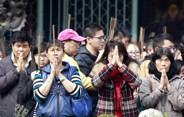 Devotees holding incense sticks pray during Chinese Lunar New Year celebrations at the Lungshan temple in Taipei February 19, 2015. (Photo by Pichi Chuang/Reuters)