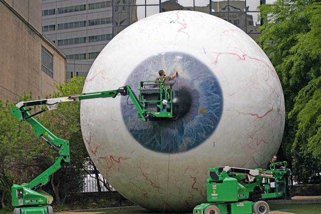 A man who asked to be identified as Worker, works on the artwork call the Eye created by artist Tony Tasset in downtown Dallas, Thursday, April 15, 2021. The 30-foot giant eye had been vandalized and the workers said they were restoring the fiberglass sculpture. (Photo by L.M. Otero/AP Photo)