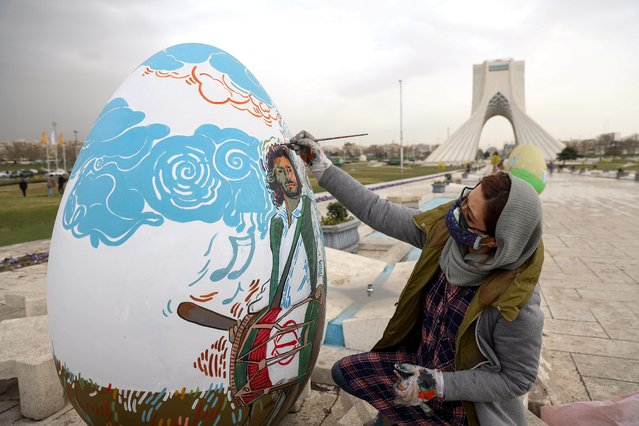 An Iranian woman paints a Nowruz-themed decoration, ahead of Nowruz, the Iranian New Year, in Tehran, Iran on March 17, 2021. (Photo by Majid Asgaripour/WANA (West Asia News Agency) via Reuters)