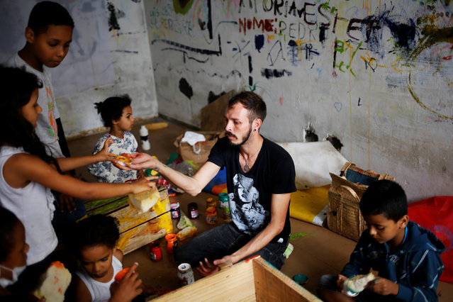 Jorge (C), 31, who is among members of lesbian, gay, bisexual and transgender (LGBT) community, that have been invited to live in a building that the roofless movement has occupied, teaches children to draw, in downtown Sao Paulo, Brazil, November 15, 2016. (Photo by Nacho Doce/Reuters)