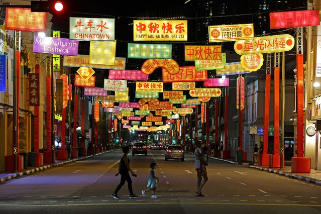 People cross a street decorated with banner like lanterns during the Mid-Autumn Festival at Chinatown on September 20, 2020 in Singapore. (Photo by Suhaimi Abdullah/Getty Images)