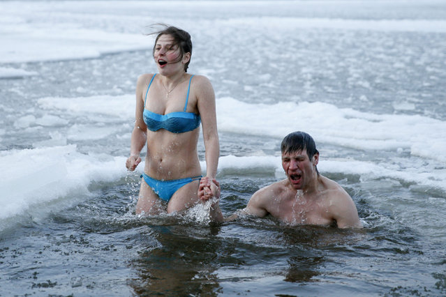 A couple takes a dip in icy waters during celebrations for the Orthodox Epiphany on the Dnipro River in Kiev, Ukraine, January 19, 2016. (Photo by Valentyn Ogirenko/Reuters)