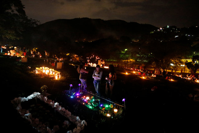 "People light candles, next to a grave in the cemetery ""Jardines de la Aurora"", to mark the beginning of the Christmas festivities, in Cali, Colombia, December 7, 2016. (Photo by Jaime Saldarriaga/Reuters)"