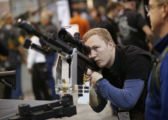 Matt Couch looks at a rife at the Barrett booth at the Shooting, Hunting and Outdoor Trade Show, Tuesday, January 19, 2016, in Las Vegas. (Photo by John Locher/AP Photo)