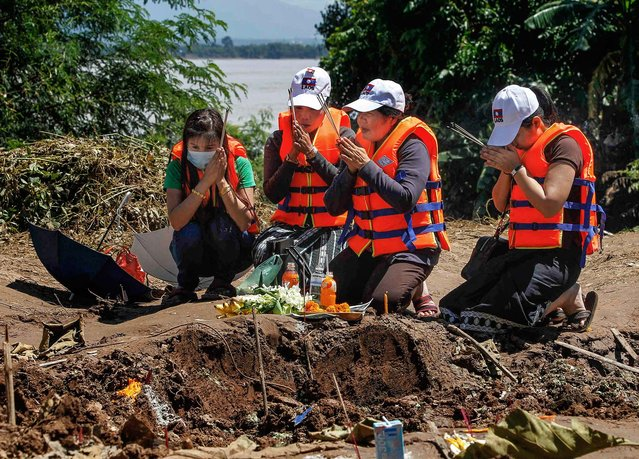 Relatives of the victims of a Lao Airlines plane crash, pray at the site of the crash near the Mekong river, on Oktober 18, 2013. Bad weather is being blamed for the crash  which plunged into the  river in southern Laos on Wednesday, killing all 49 people on board. The plane crashed five miles short of its destination Pakse, which is near the borders of both Thailand and Cambodia. (Photo by Chaiwat Subprasom/Reuters)
