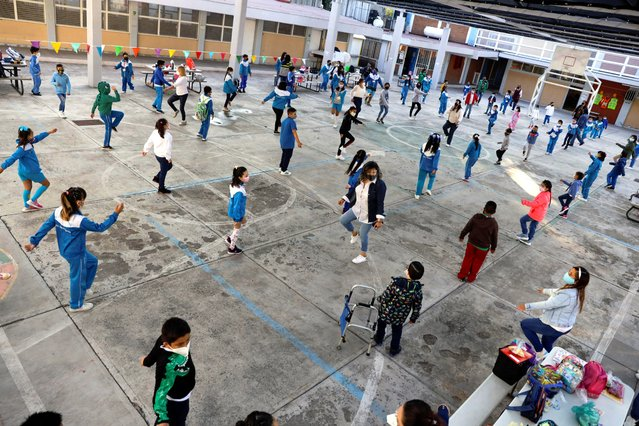 Children stretch before entering their classrooms at the Ignacio Zaragoza elementary school as Mexico City's authorities resumed in-person classes today after a downward trend in the number of infections and hospitalisations of the coronavirus disease (COVID-19), in Mexico City, Mexico on June 7, 2021. (Photo by Luis Cortes/Reuters)