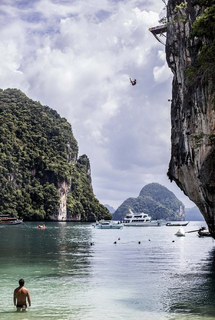 In this handout image provided by Red Bull, Artem Silchenko of Russia dives from the 27 metre platform at training on Hong Island in the Andaman Sea as David Colturi (bottom) of the USA watches on during the final stop of the 2013 Red Bull Cliff Diving World Series on October 25, 2013 at Krabi, Thailand. (Photo by Dean Treml/Red Bull via Getty Images)