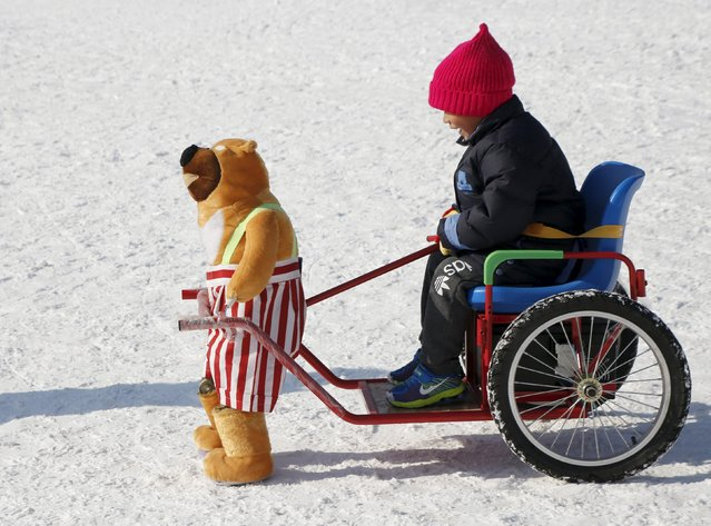 A boy rides on a snow wagon towed by a robot dressed as a stuffed doll, which only moves forward by moving its legs, during the Ice and Snow carnival at Taoranting park in Beijing, China, January 25, 2016. (Photo by Kim Kyung-Hoon/Reuters)