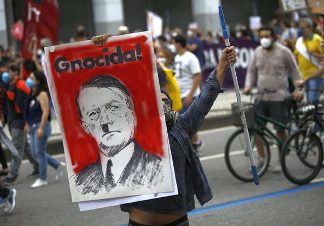 A protester holds a poster depicting Brazilian President Jair Bolsonaro as Adolf Hitler and the Portuguese word for genocidal, during a demonstration against Bolsonaro's handling of the coronavirus pandemic and economic policies protesters say harm the interests of the poor and working class, in Rio de Janeiro, Brazil, Saturday, June 19, 2021. (Photo by Bruna Prado/AP Photo)