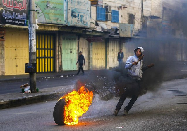 A Palestinian runs near a burning tire during clashes with Israeli security forces following the funeral of Anas al-Atrash, 23, in the West Bank city of Hebron, on November 8, 2013. Israeli troops shot and killed al-Atrash who tried to stab one of the soldiers at a West Bank checkpoint, a police spokesman said. (Photo by Mohamad Torokman/Reuters)