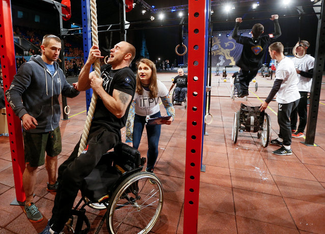 "Participants perform during the final stage of the ""Games of Heroes"" crossfit competition for Ukrainian servicemen, who became disabled after getting wounded during a military conflict in the east of the country, in Kiev, Ukraine, December 24, 2016. (Photo by Valentyn Ogirenko/Reuters)"