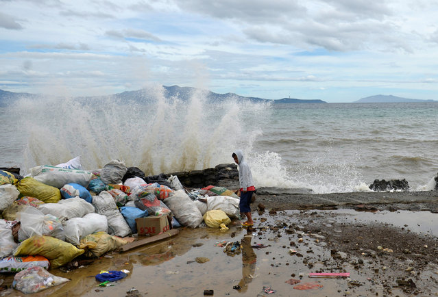 A boy stands at a partially damaged port, as strong waves hit the shore after Typhoon Nock-Ten hit Mabini, Batangas, in the Philippines December 26, 2016. (Photo by Ezra Acayan/Reuters)