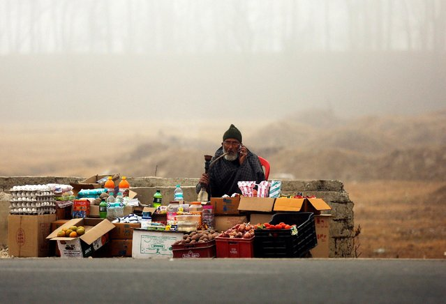 A roadside vendor smokes a water pipe as he waits for customers on a foggy winter morning, on the outskirts of Srinagar, December 13, 2016. (Photo by Danish Ismail/Reuters)