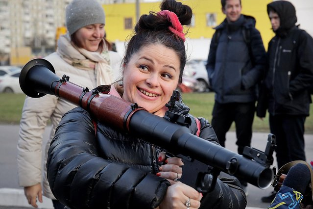 A woman poses with a grenade launcher at a weapons exhibition during festivities marking Marines Day in St.Petersburg, Russia, Saturday, November 24, 2018. (Photo by Dmitri Lovetsky/AP Photo)