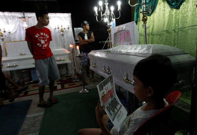 Grieving relatives attend the wake of Analyn Diamla, 22 (not pictured), Ednel Santor, 22 (L) and Kristine Santor, 44 (R), who according to police were killed by unidentified gunmen at a drug den, in Caloocan city, Metro Manila, Philippines December 30, 2016. (Photo by Czar Dancel/Reuters)