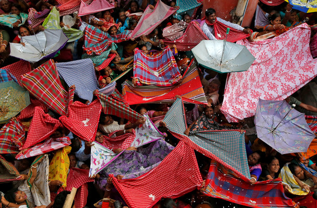 Hindu devotees hold up clothes and umbrellas to receive rice as offerings being distributed by a temple authority on the occasion of the Annakut festival in Kolkata, India, November 8, 2018. (Photo by Rupak De Chowdhuri/Reuters)