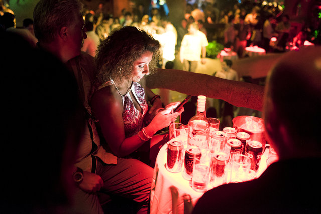 A clubgoer checks her phone inside the Baby O nightclub on April 2, 2015 in Acapulco, Mexico. (Photo by Jonathan Levinson/The Washington Post)