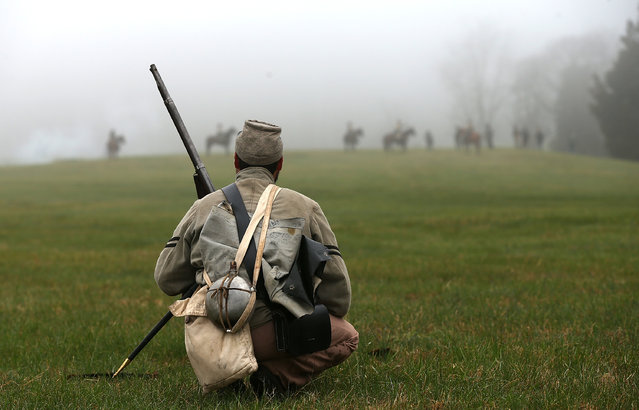 An American Civil War re-enactor dressed as a member of the North Carolina 26th infantry watches Union cavalry take their position during a re-enactment of the Battle of Appomattox Court House at the Appomattox Court House National Historical Park April 9, 2015 in Appomattox, Virginia. (Photo by Win McNamee/Getty Images)
