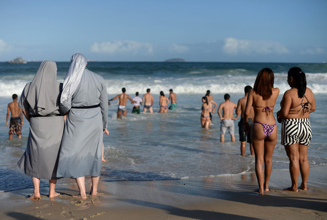 Two Polish nuns look at people bathing as hundreds of thousands of young Catholic pilgrims attending World Youth Day (WYD) start gathering at Copacabana beach in Rio de Janeiro for a prayer vigil with Pope Francis, on July 27, 2013. (Photo by Yasuyoshi Chiba/AFP Photo)