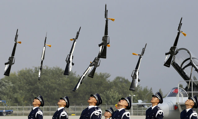 Members of a South Korean Air Force honor guard throw their guns in the air during a press day of an air show as part of the Seoul International Aerospace & Defense Exhibition which will be held from October 25 to November 3, at Cheongju International Airport in Cheongju, south of Seoul, South Korea, Thursday, October 24, 2013. (Photo by Lee Jin-man/AP Photo)