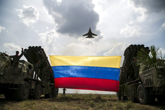 """A Russian-made Sukhoi Su-30MKV fighter jet of the Venezuelan Air Force flies over a Venezuelan flag tied to missile launchers, during the """"Escudo Soberano 2015"""" (Sovereign Shield 2015) military exercise in San Carlos del Meta in the state of Apure April 15, 2015. (Photo by Marco Bello/Reuters)"""