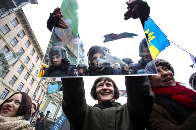 A pro-European integration supporter stands holding a mirror opposite a police line blocking the government quarter in Kiev, December 30, 2013. (Photo by Maxim Zmeyev/Reuters)