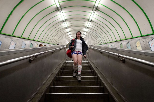 """A participant in the13th annual International """"No Pants Subway Ride"""" enters a London underground station in London, on January 12, 2014. (Photo by Leon Neal/AFP Photo)"""