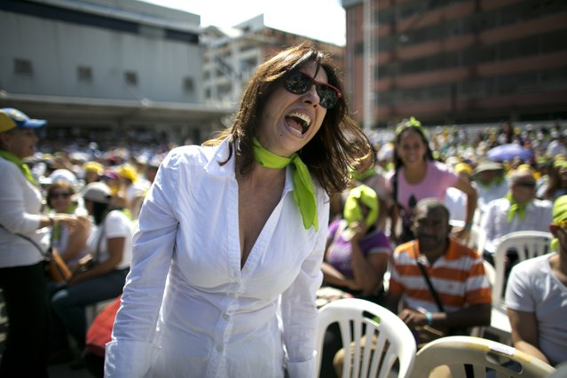 A woman yells during an event to swear in nurses, doctors, professionals and others, as the group that will help with the arrival and distribution of humanitarian aid in Venezuela, in Caracas, Venezuela, Saturday, February 16, 2019. The U.S. Air Force has begun flying tons of aid to a Colombian town on the Venezuelan border as part of an effort meant to undermine socialist President Nicolas Maduro. The first of three C-17 cargo planes has flown from Homestead Air Reserve Base in Florida and landed in the town of Cucuta. (Photo by Ariana Cubillos/AP Photo)