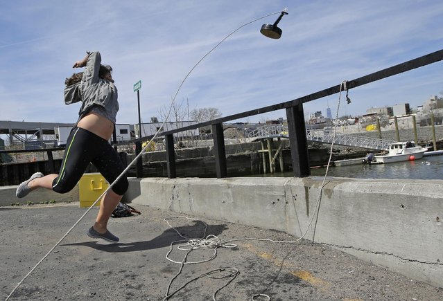 Women's division winner 18 year-old Nada Zimmermann of Innsbruck, Austria, hurls a banjo into a heavily polluted New York waterway during the fifth annual Brooklyn Folk Festival's Gowanus Banjo Toss, Sunday, April 19, 2015, in the Brooklyn borough of New York. (Photo by Kathy Willens/AP Photo)