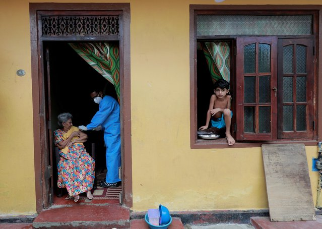 An elderly woman receives a dose of Sinopharm vaccine at her home from the Sri Lanka Army mobile vaccination unit against the coronavirus disease (COVID-19) in Colombo, Sri Lanka, September 14, 2021. (Photo by Dinuka Liyanawatte/Reuters)