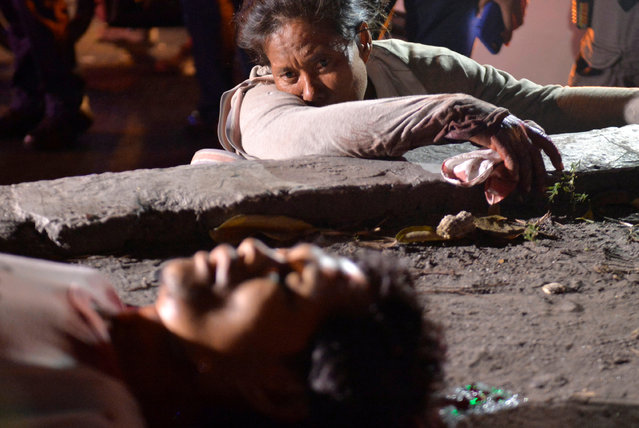 Sentimina Bananga weeps next to the body of her partner Jimmy Said, who according to her was shot dead by an unidentified gunman in a motorcycle while they were begging in the street, in Manila, Philippines on January 21, 2017. (Photo by Ezra Acayan/Reuters)