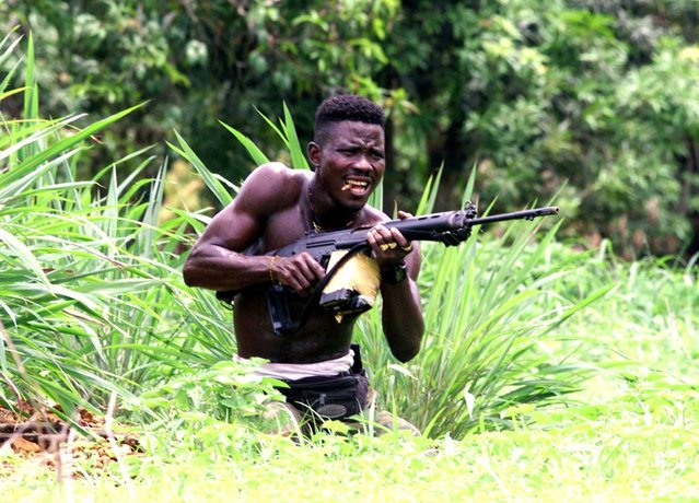 A pro-government Sierra Leonean fighter bites a bullet as he takes position in no man's land 2 km ahead of Rogberi junction where evidence of executed UN troops were found after heavy fighting between government troops and RUF rebels 100 km north east of Freetown, Sierra Leone, May 23, 2000. (Photo by Yannis Behrakis/Reuters)