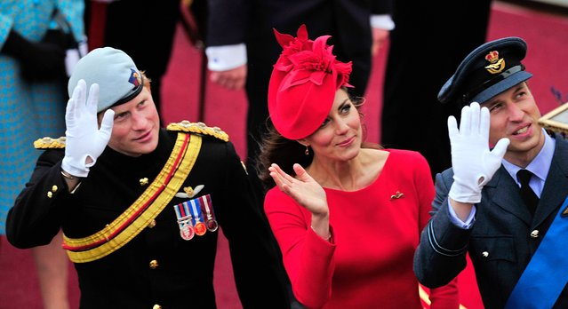 """Britain's Catherine, Duchess of Cambridge, (C) Prince William (R) and Prince Harry (L) wave as they pass the Houses of Parliament aboard the Royal barge, """"Spirit of Chartwell"""" in central London, on June 3, 2012, during the Thames Diamond Jubilee Pageant. (Photo by Glyn Kirk/AFP Photo)"""