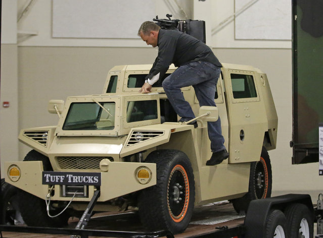 "Sam Warren climbs in to a prototype combat vehicle during the PrepperCon expo Friday, April 24, 2015, in Sandy, Utah. Hundreds of survivalists and ""preppers"" are gathering in the Salt Lake City suburb of Sandy for the first annual PrepperCon, featuring demonstrations of underground bunkers, food storage, and armored vehicles. (Photo by Rick Bowmer/AP Photo)"
