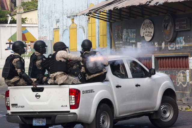 A National Police officer fires tear gas at protesters who are demanding the resignation of Haitian President Jovenel Moise near the presidential palace in Port-au-Prince, Haiti, Tuesday, February 12, 2019. Protesters are angry about skyrocketing inflation and the government's failure to prosecute embezzlement from a multi-billion Venezuelan program that sent discounted oil to Haiti. (Photo by Dieu Nalio Chery/AP Photo)