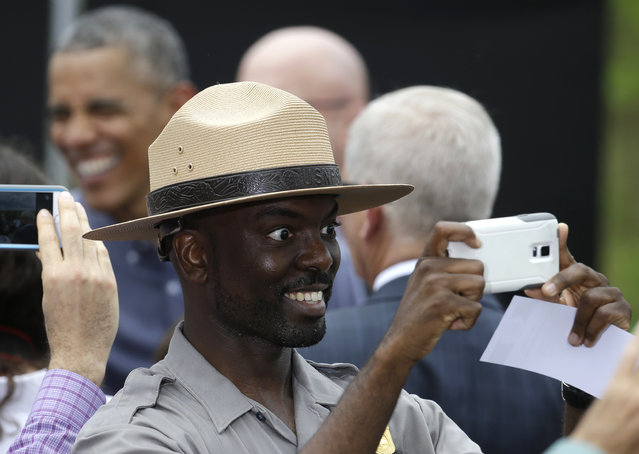 An employee of the National Park Service takes a selfie with President Barack Obama, left, in the background meeting with the crowd after a tour of Everglades National Park on Earth Day, Wednesday, April 22, 2015, in Florida. Obama used the visit  to warn of the damage that climate change is already inflicting on the nation's environmental treasures. (Photo by Lynne Sladky/AP Photo)